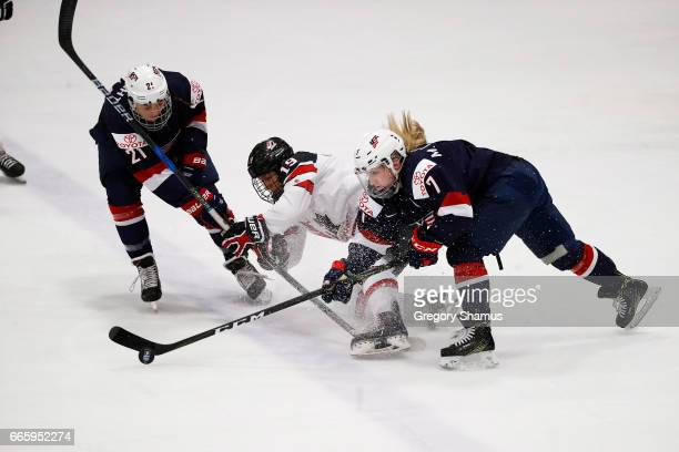 Brianne Jenner of Canada tries to split the defense of Monique Lamoureux and Hilary Knight of the United States during the first period in the gold...