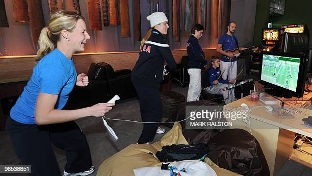 Brianne Lea McLaughlin and Gigi Marvin from the USA Ice Hockey team play a video game as they relax in the Winter Olympic athletes Living Room during...