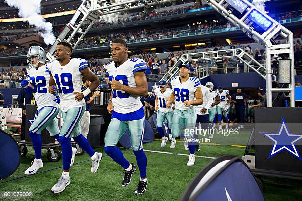 Brice Butler, Gavon Escobar and Tyrone Crawford of the Dallas Cowboys runs onto the field before a preseason game against the Houston Texans at AT&T...