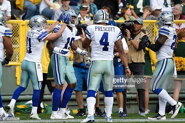 Brice Butler of the Dallas Cowboys is congratulated by his teammates after scoring a second quarter touchdown against the Green Bay Packers during...