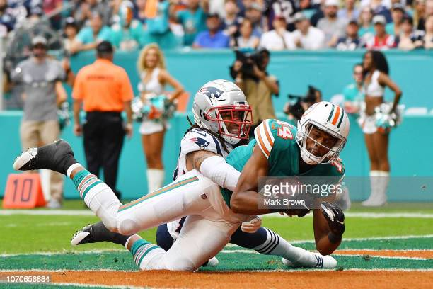 Brice Butler of the Miami Dolphins completes a pass for a touchdown against the defense of Stephon Gilmore of the New England Patriots during the...