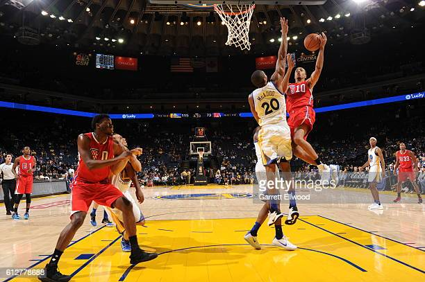Brice Johnson of the Los Angeles Clippers goes to the basket against James Michael McAdoo of the Golden State Warriors during a preseason game on...