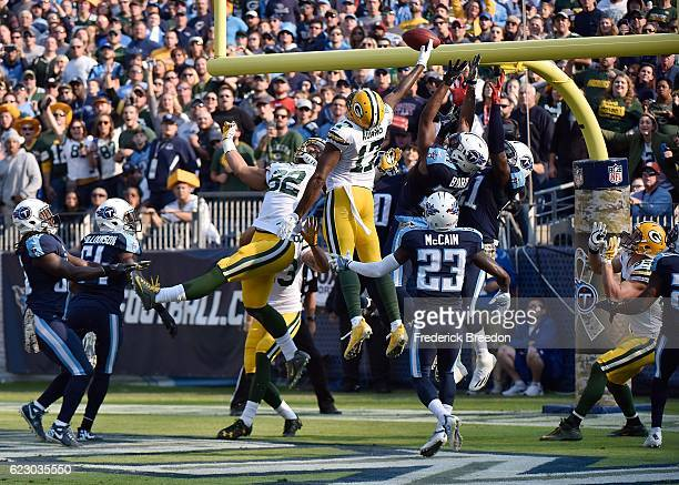 Brice McCain of the Tennessee Titans watches Davante Adams of the Green Bay Packers jump up to try to catch a hail mary pass at the end of the half...