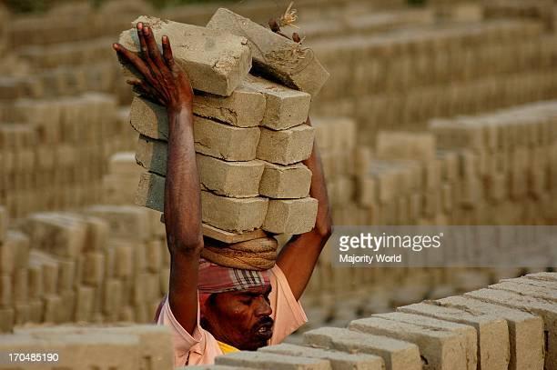 Brick field workers pilesup raw bricks for burning Dhaka Bangladesh January 16 2007