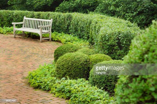 Brick Garden Patio and Wood Bench in Lush Planted Landscape