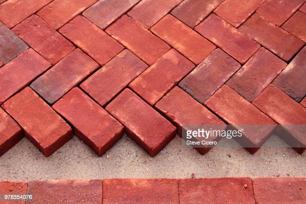 brick herriingbone pattern installation - paving stone stock pictures, royalty-free photos & images