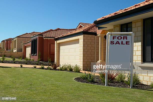 Brick house with a 'For Sale' sign in front yard