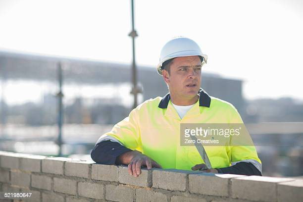 Brick layer using trowel on construction site wall