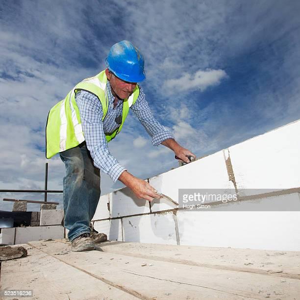 brick layer working on construction site - hugh sitton photos et images de collection