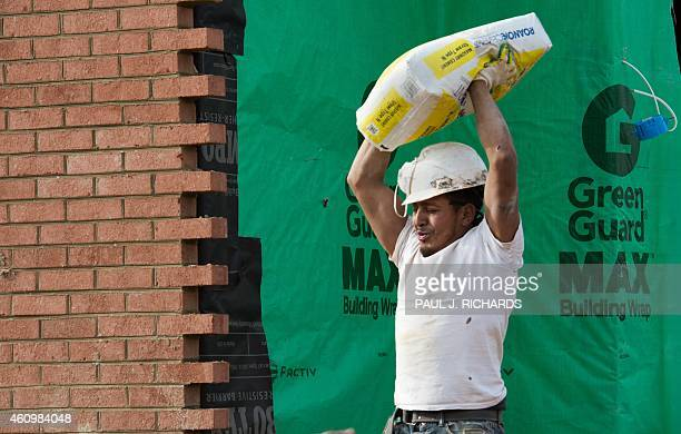 A brick mason helper carries a heavy bag of a cement to the mixer as a construction crew covers a new home in bricks in Ashburn Virginia on January 2...