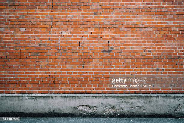 brick wall and sidewalk - brick wall stock pictures, royalty-free photos & images
