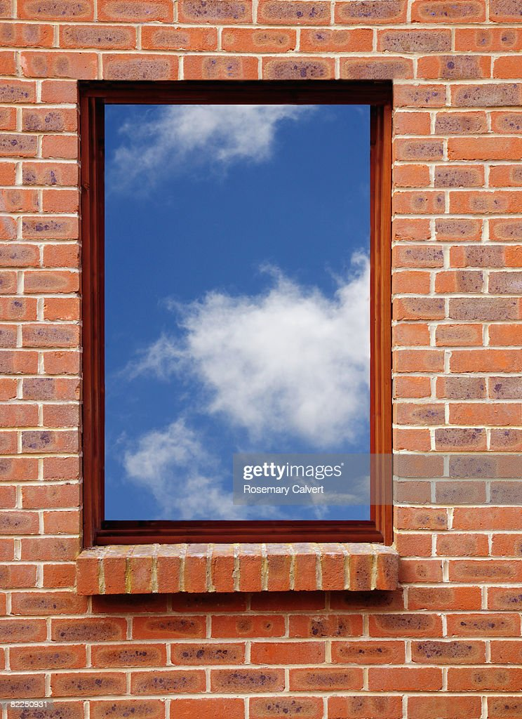 Brick wall of a house with a window : Stock Photo