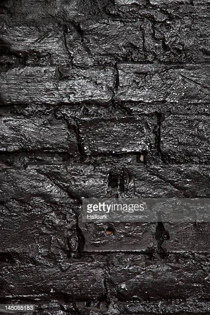 A brick wall painted black, full frame