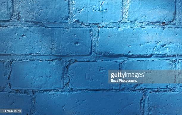 brick wall painted in blue - wall building feature stock pictures, royalty-free photos & images