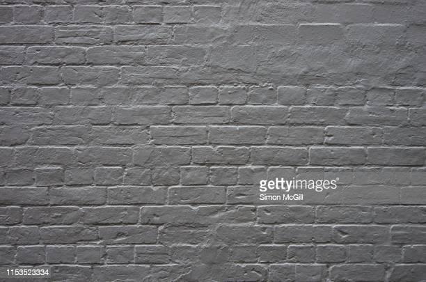 brick wall painted white - erosionado fotografías e imágenes de stock