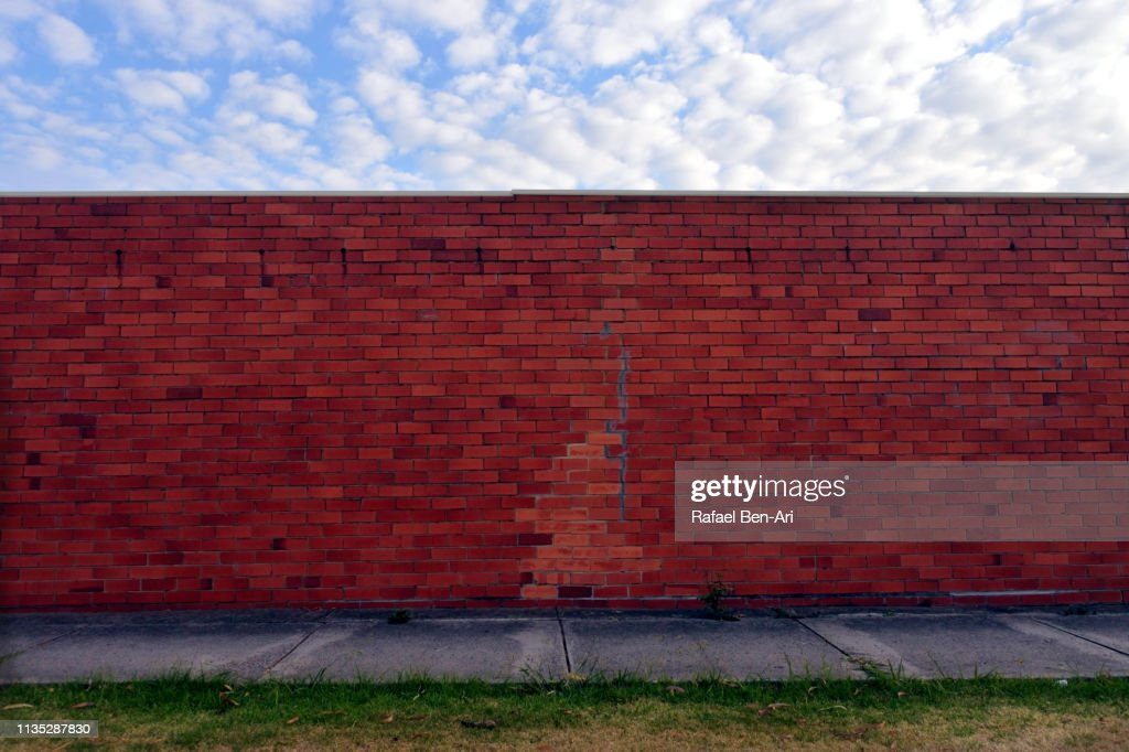 Brick wall under a cloudy sky in urban city sidewalk : Stock Photo