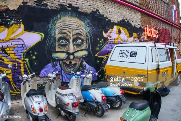 Brick Wall with Graffiti Art Vespa Scooters and an Old VW Bus at Fabrika on August 09 2018 in Tbilisi Georgia