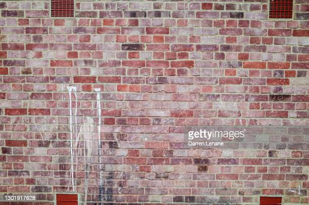 a brick wall with paint splatter - brick wall stock pictures, royalty-free photos & images