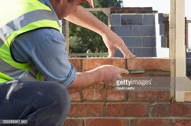 Bricklayer building wall, close-up