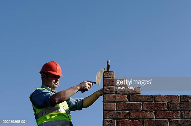 bricklayer building wall, side view - 7894 stock pictures, royalty-free photos & images