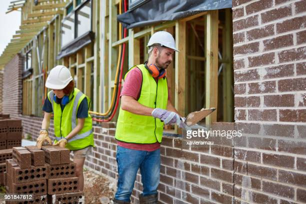 Bricklayer cementing bricks with trainee at site