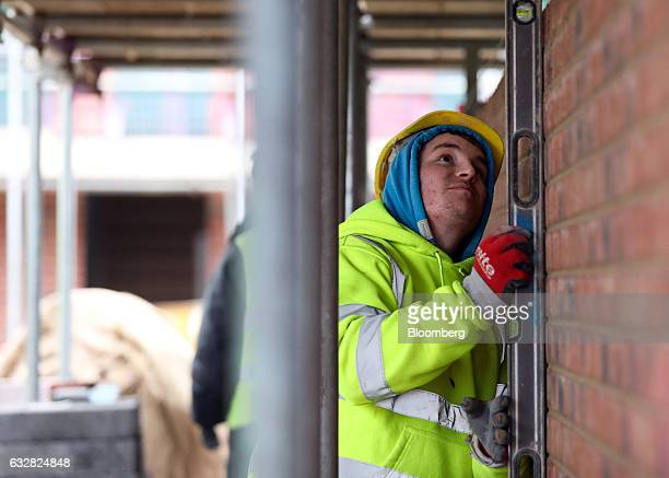 A bricklayer checks the alignment of a wall on a Persimmon Plc residential property construction site in WestonSuperMare UK on Thursday Jan 26 2017...