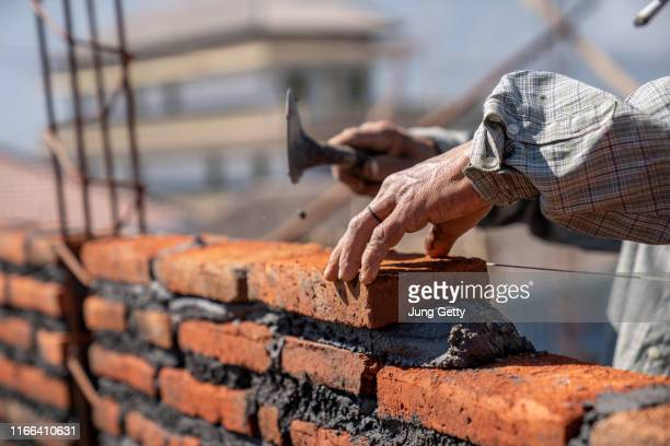 bricklayer industrial worker installing brick masonry with trowel putty knife at construction site - rebuilding stock pictures, royalty-free photos & images