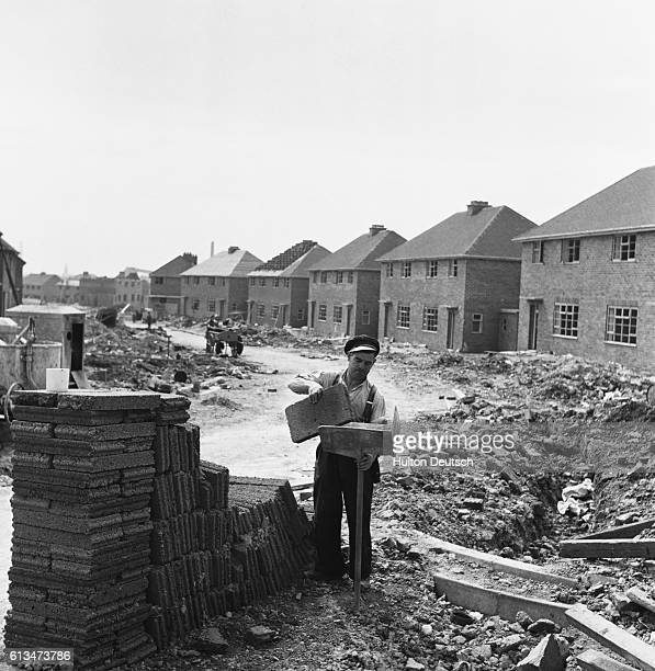 A bricklayer loads up his hod with breeze blocks on the site of a new housing estate built as part of the postwar programme aiming to construct 30000...