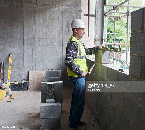Bricklayer placing cinder bloc on building site