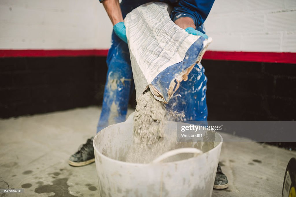 Bricklayer pouring cement powder in bucket : Stock Photo