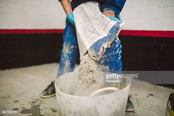 bricklayer pouring cement powder in bucket - cement stock pictures, royalty-free photos & images