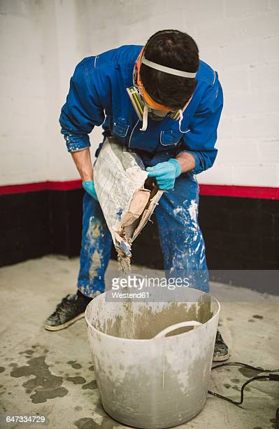Bricklayer preparing cement, pouring water in bucket