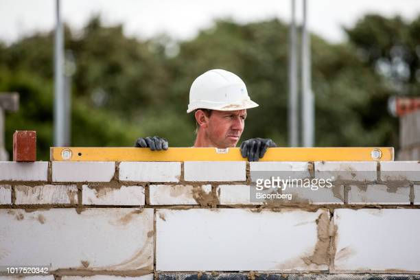 A bricklayer uses a spirit level to check a wall on flats being built on a Persimmon Plc residential construction site in Grays UK on Tuesday Aug 14...