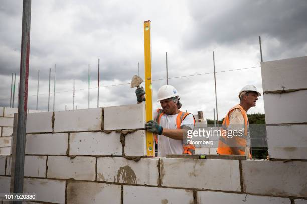 A bricklayer uses a spirit level to checks the angle of a breeze block wall on flats being built on a Persimmon Plc residential construction site in...
