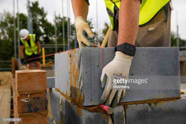 Bricklayer uses wearable technology, which vibrates when wearer breaches social distancing guidelines, on a Bewley Homes Plc residential construction...