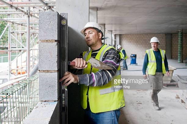 Bricklayer using spirit level to check brick laying
