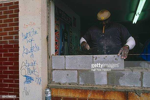 A bricklayer walls up an entrance at the CabriniGreen housing project in Chicago The construction workers are repairing a building in the housing...