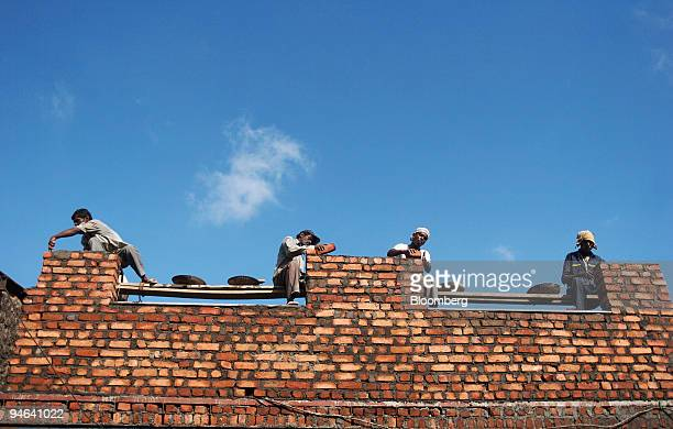 Bricklayers work on an illegal construction building in the Dharavi slum area of Mumbai India on Tuesday June 5 2007 The development program for...