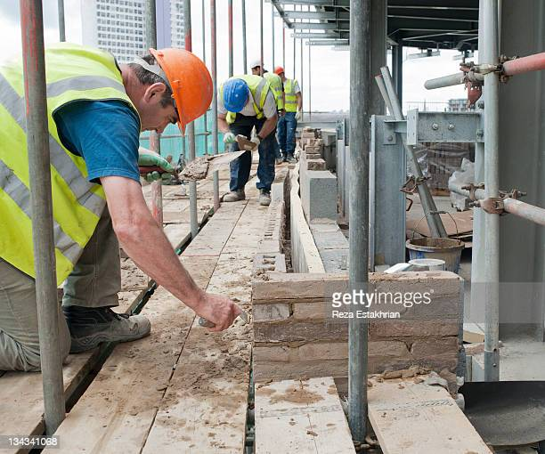 bricklayers work on construction site - newpremiumuk stock pictures, royalty-free photos & images