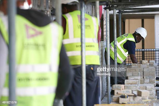 Bricklayers work on the external facade of an apartment building at a Countryside Properties Plc brownfield regeneration residential construction...