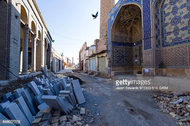 Bricks and building materials fill a dusty street during a Mosque renovation.