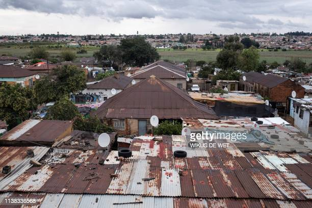 Bricks and car tyres are seen on top of the roof's of buildings on April 5 2019 in Kliptown near Soweto South Africa goes to the polls next month the...