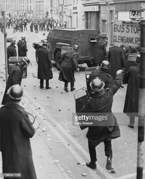 Bricks and rocks litter the streets as members of the Royal Ulster Constabulary take shelter behind their shields and an armoured van as trouble...