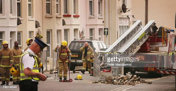 Bricks lay in the street as firemen attend the scene after an earthquake caused damage to houses on April 28, 2007 in Folkstone, Kent. The earth...