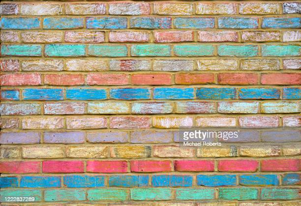 brickwork painted with rainbow colours during the coronavirus epidemic - brick wall stock pictures, royalty-free photos & images