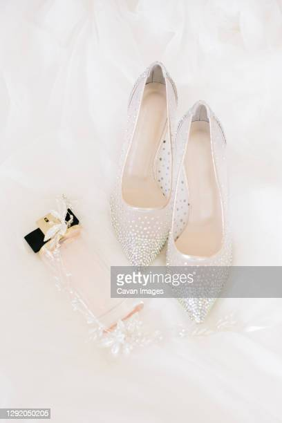 bridal accessories. bridal shoes, perfume and crown. - wedding dress stock pictures, royalty-free photos & images