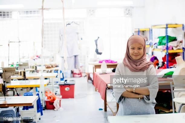 Bridal and fashion designer pose inside her workshop