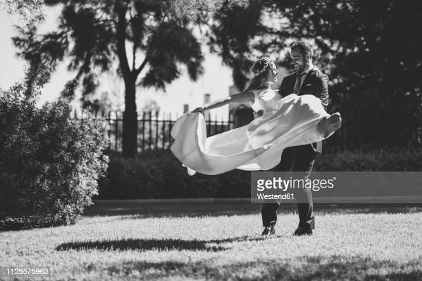 bridal couple enjoying wedding day in a park - marriage stock pictures, royalty-free photos & images