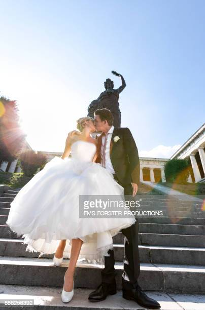 bridal couple kissing in front of statue of Bavaria in Munich on a sunny day