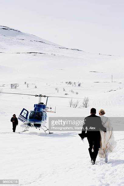 bridal couple walking towards a waiting helicopter, sweden. - helicopter photos stock pictures, royalty-free photos & images